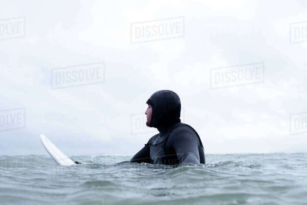 Surfer wearing wetsuit floating with board in wintery sea Royalty-free stock photo