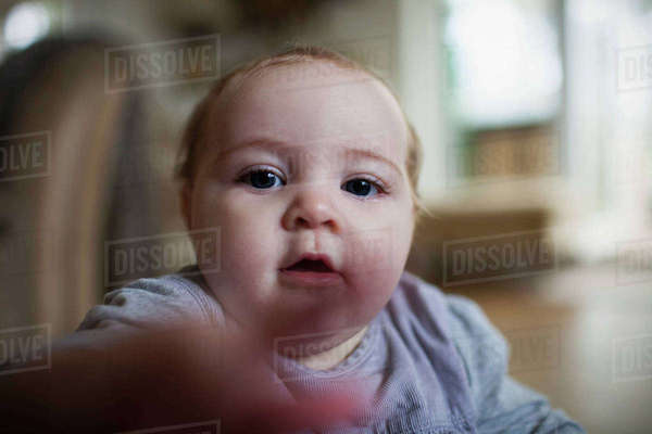 Baby girl sitting on floor and reaching towards camera Royalty-free stock photo