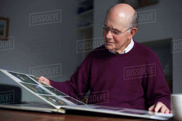 Senior man looking through photo album at home Royalty-free stock photo