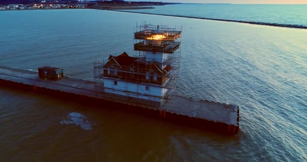 Lighthouse surrounded by scaffolding, under renovation or construction at sunrise. Still doing it's job, still beautiful in the dramatic light of dawn. Royalty-free stock video