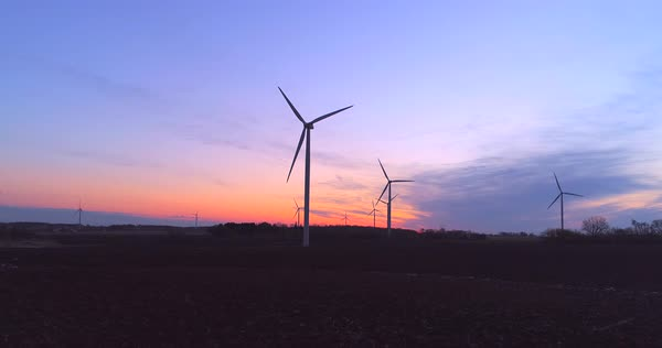 Moving aerial view of giant wind turbines backlit by the dawn sky. Royalty-free stock video
