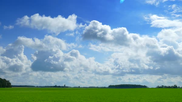 Fluffy, billowy clouds drift over lush green rural landscape. Royalty-free stock video
