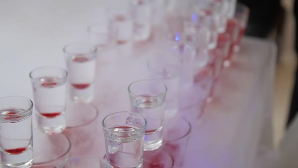 Trick bartending domino effect as shot glasses fall into pink cocktails Royalty-free stock video