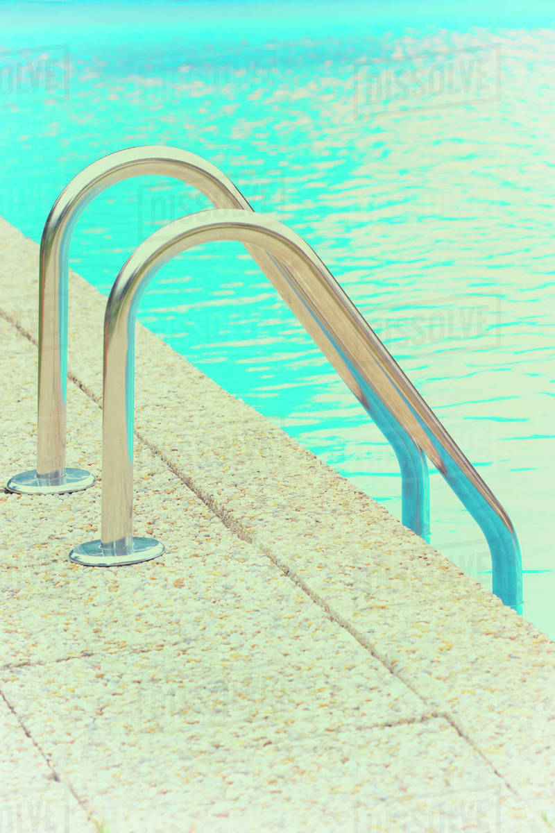 Swimming pool railings ladder steps chrome rail stock photo