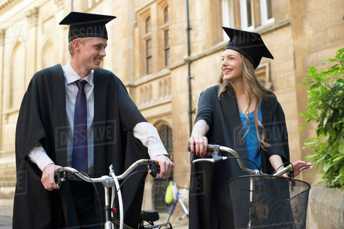 Two young students in graduation gowns cycling through the grounds ...