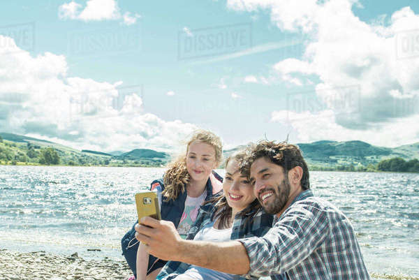 Three people taking a selfie on the shore beside Bala Lake in Wales Royalty-free stock photo