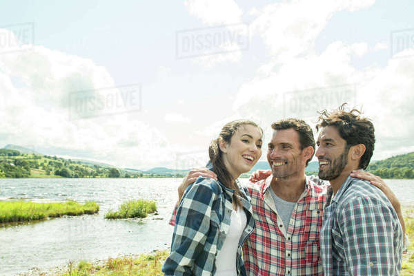 Three friends standing smiling on the shore of Bala Lake in Wales Royalty-free stock photo