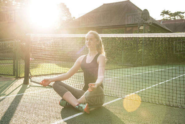 A young woman holding a yoga pose in the evening sunshine on a tennis court Royalty-free stock photo