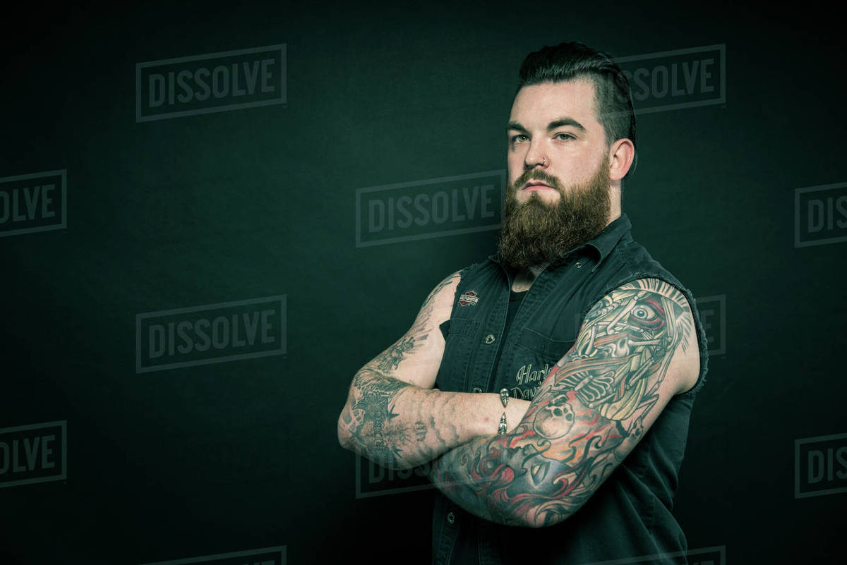 cc550695c Studio portrait of a bearded man with tattooed arms - Stock Photo ...