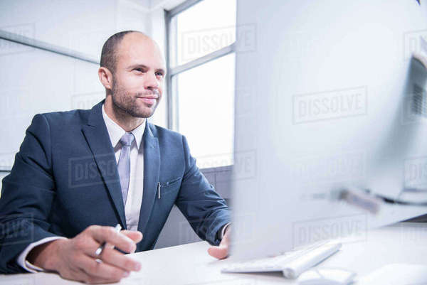 A professional man sitting in front of a computer in an office environment Royalty-free stock photo