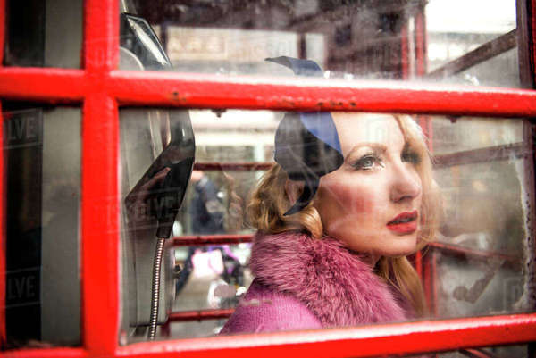 A stylish young woman dressed in 1930s style clothing standing in a traditional telephone kiosk on a London street Royalty-free stock photo
