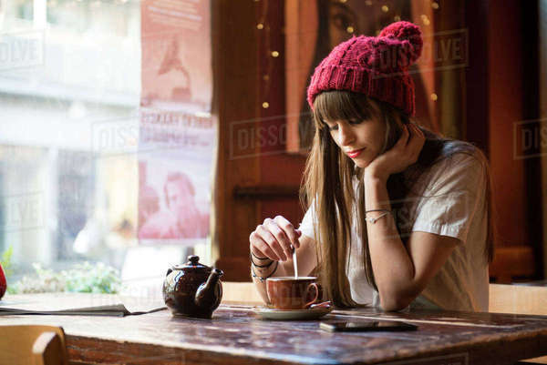 A young woman sitting at a table in a coffee shop in Manchester Royalty-free stock photo