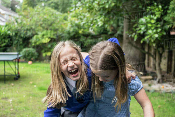 Two ten year old girls in school uniform laughing together outside Royalty-free stock photo