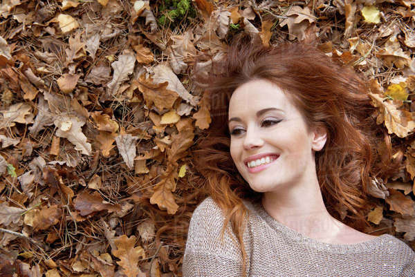 An attractive young woman laying on the forest floor surrounded by leaves Royalty-free stock photo
