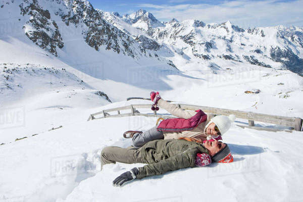 Laughing senior couple laying in snow on mountain Royalty-free stock photo