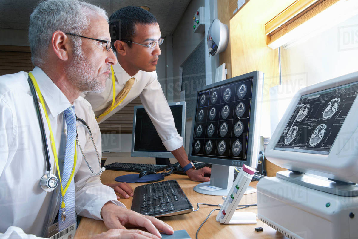 Surgeon And Radiologist Viewing Digital Brain Scan In Hospital