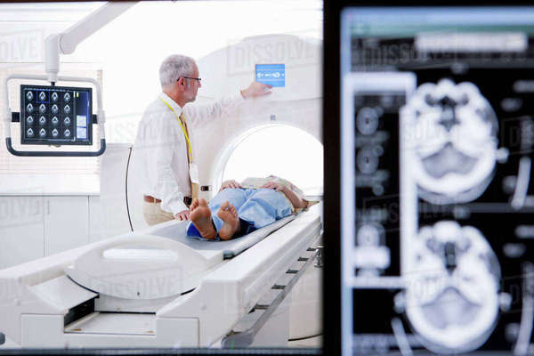 Doctor and patient at CT scanner in hospital with digital brain scan in foreground Royalty-free stock photo