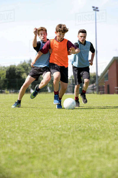 Middle schoolboys running playing soccer on field in physical education class Royalty-free stock photo