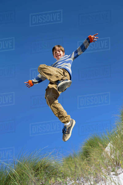 Exuberant boy jumping for joy over sand dune beach grass Royalty-free stock photo