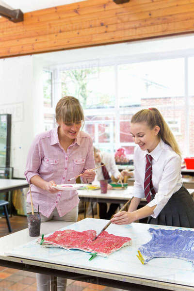 Art teacher guiding middle school student painting in art class Royalty-free stock photo