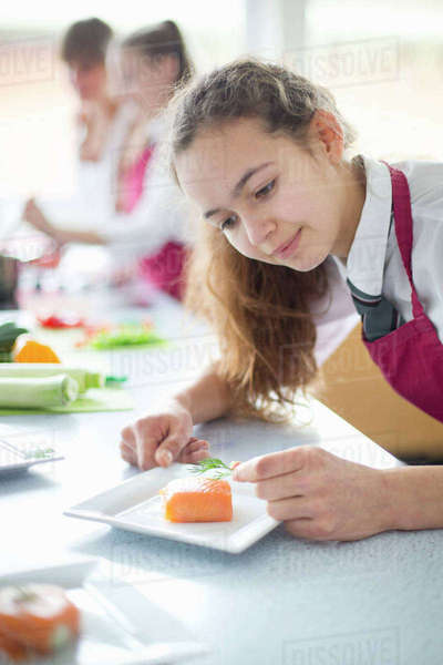 Focused high school student plating food in home economics class Royalty-free stock photo