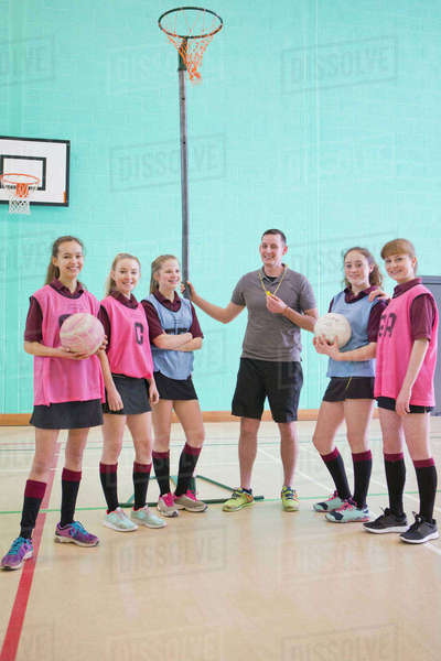 Portrait smiling gym teacher and high school students with volleyballs Royalty-free stock photo