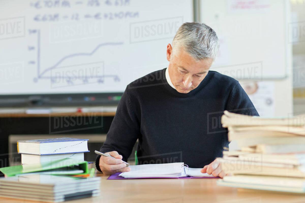 teacher grading homework in classroom stock photo dissolve