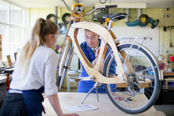 Teacher and female high school student assembling bicycle in woodworking class Royalty-free stock photo