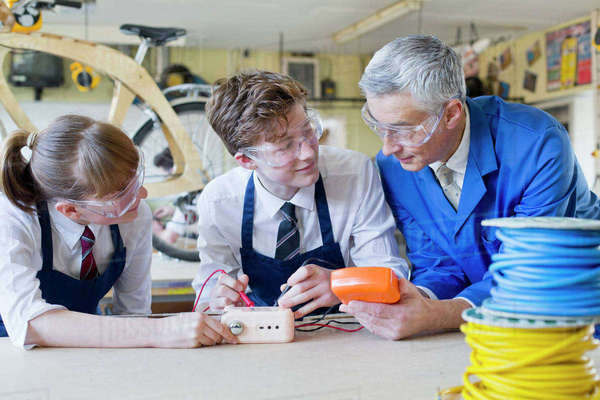 Teacher guiding high school students with electronics in shop class Royalty-free stock photo