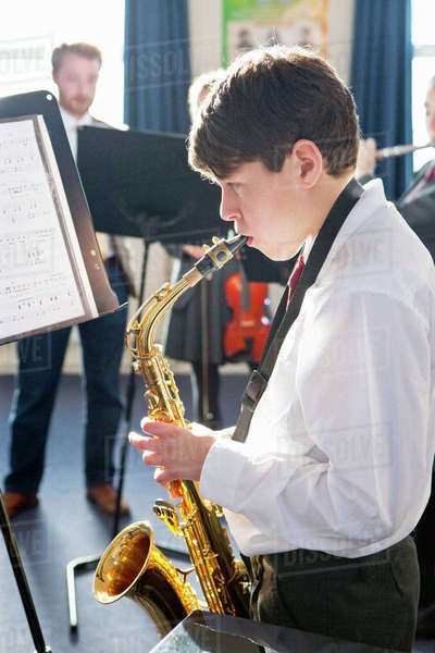 Middle school student playing saxophone at sheet music in music class Royalty-free stock photo