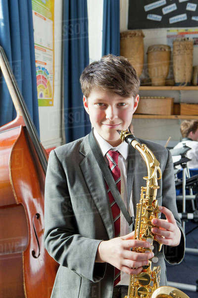 Portrait confident middle school student with saxophone in music classroom Royalty-free stock photo