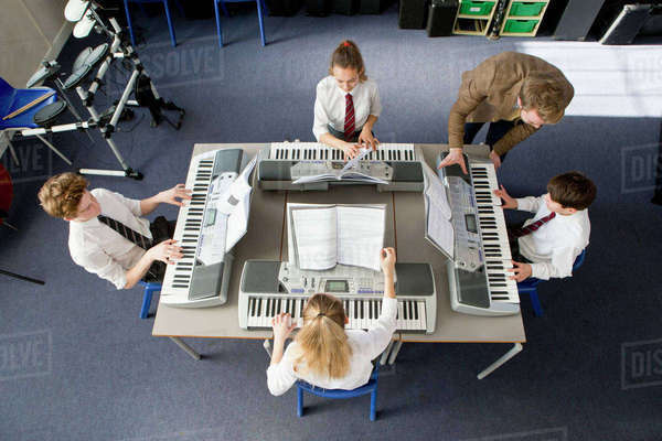 Music teacher teaching middle school students playing pianos in music class Royalty-free stock photo