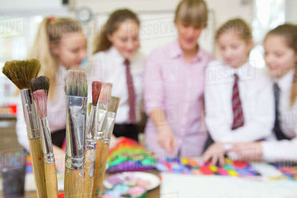 Paintbrushes in foreground with art teacher teaching middle school students painting in art class Royalty-free stock photo