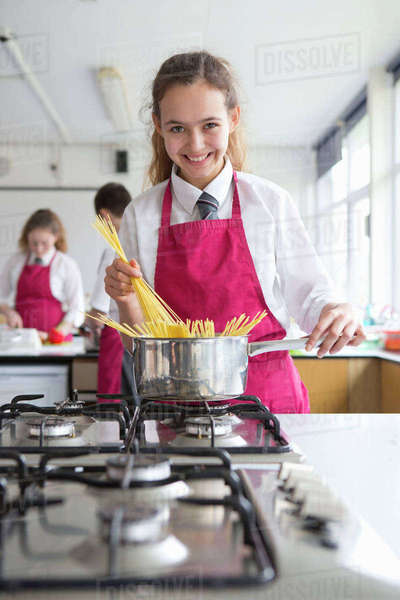 Portrait smiling high school student cooking pasta in home economics class Royalty-free stock photo