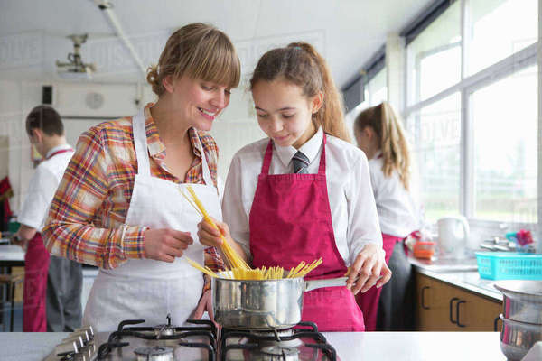 Home economics teacher teaching high school student pasta cooking Royalty-free stock photo