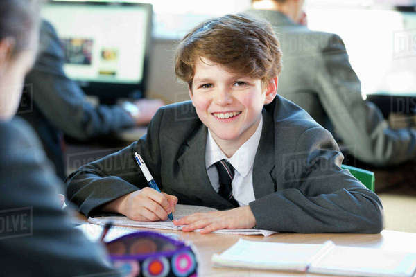 Portrait smiling middle school student doing homework in study hall Royalty-free stock photo
