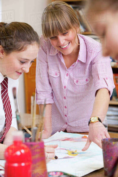 Art teacher teaching middle school student painting in art class Royalty-free stock photo