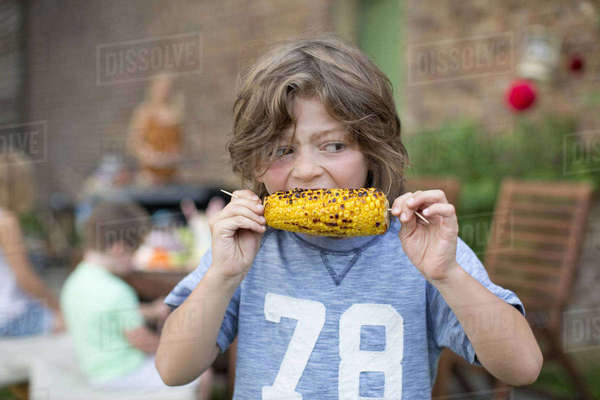 Boy Eating Sweetcorn Outdoors At Home In Garden Royalty-free stock photo