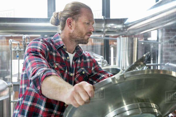 Male brewery worker checking fermentation process in steel vat Royalty-free stock photo