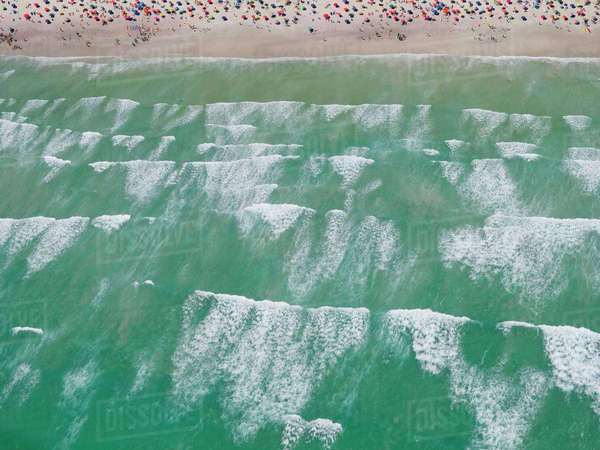 Aerial view of ocean breakers and tourists on sunny beach Royalty-free stock photo