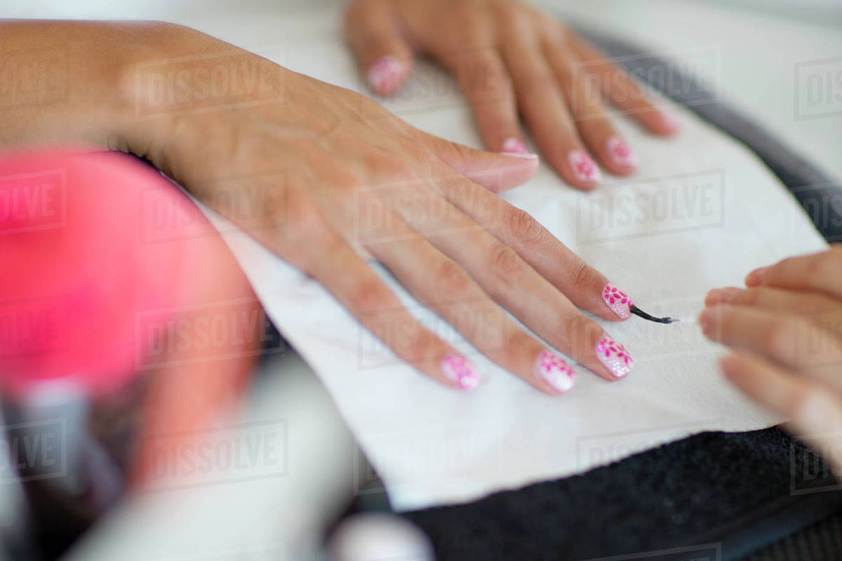 Nail technician applying fingernail polish to woman\'s fingernails ...