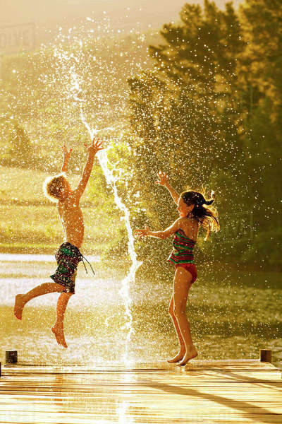 Young boy and girl jumping in air on jetty through splash of water Royalty-free stock photo