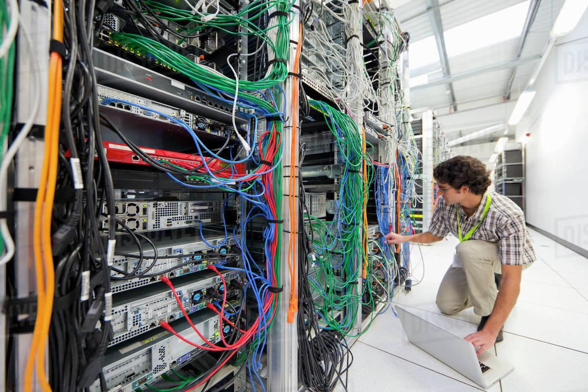 Technician Kneeling Working On Laptop Computer In Server Room Of Data Center Wiring