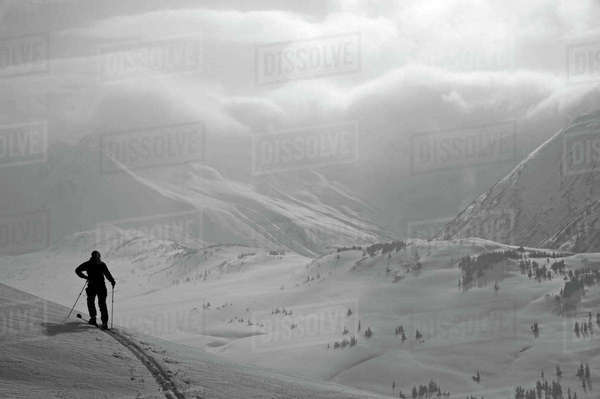 A Backcountry Skier Stands On A Ridge In Turnagain Pass, Southcentral, Alaska Rights-managed stock photo