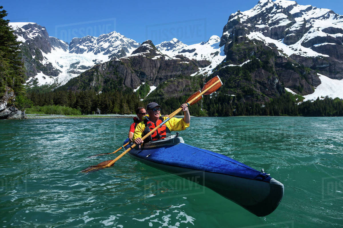 two middle aged men kayak in thumb cove with spruce glacier hanging