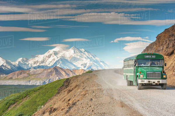 Scenic view of Mt. McKinley with a tour bus on the Park Road in the foreground, Denali National Park, Interior Alaska, Summer Rights-managed stock photo