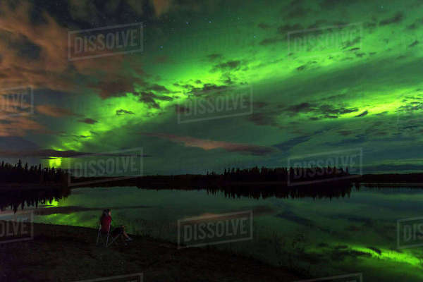 Woman views green aurora borealis over chena River Lakes, Fox, Interior Alaska, Autumn Rights-managed stock photo