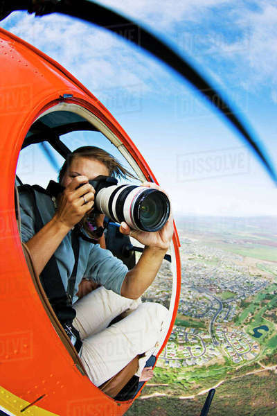 USA, Hawaii Islands, Female Photographer Shooting From Helicopter; Maui Rights-managed stock photo