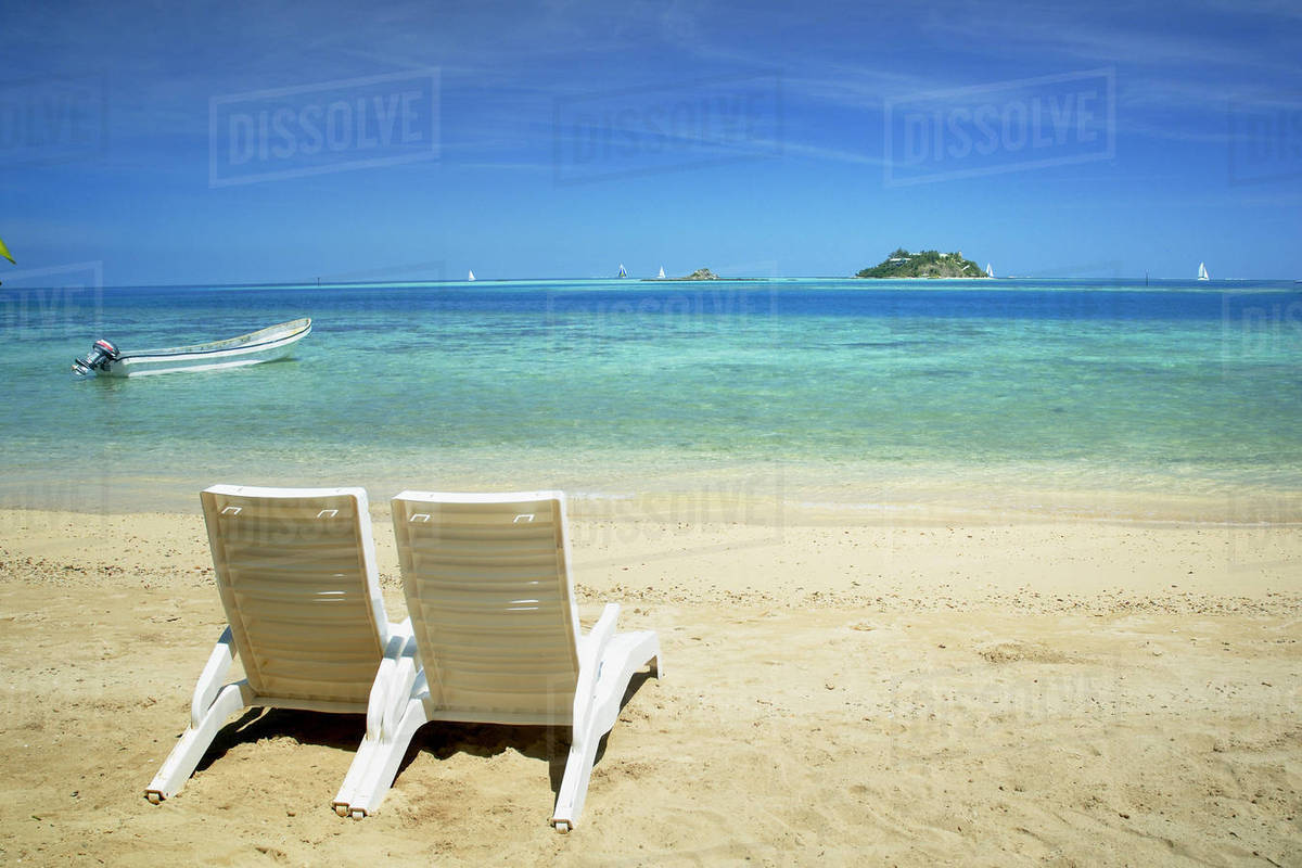 Fiji Mamanuca Islands Beach With Two Chairs Facing Out Towards Clear Blue Ocean Nwadingi Island In Distance Malolo