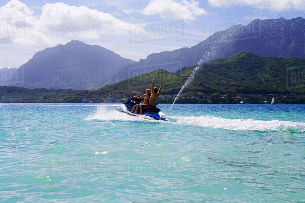 Hawaii, Oahu, Kaneohe, Young People Riding Jetski Out To The Sandbar Or Dissapearing Island Rights-managed stock photo